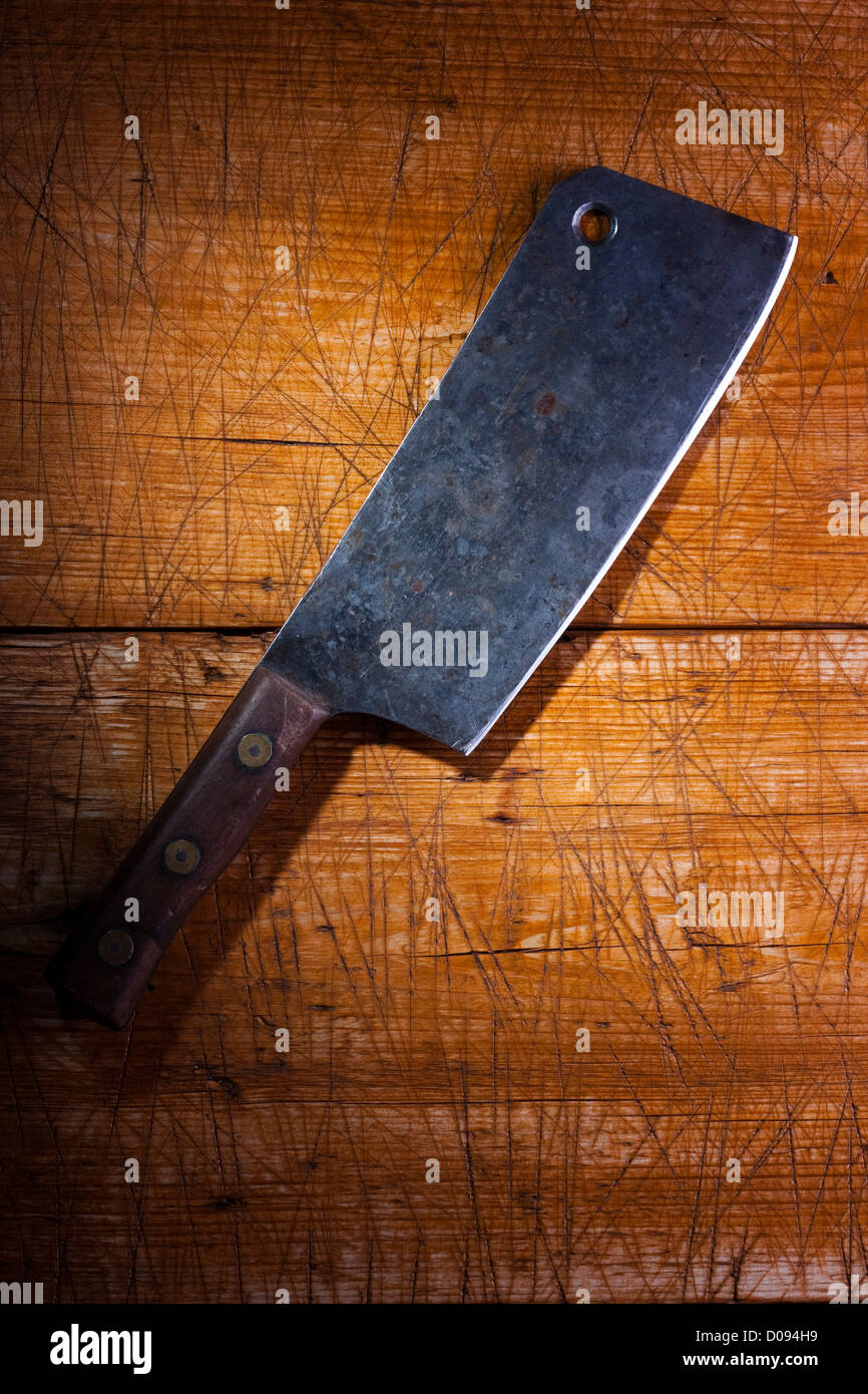 Old butcher's cleaver on a wooden desk - Stock Image