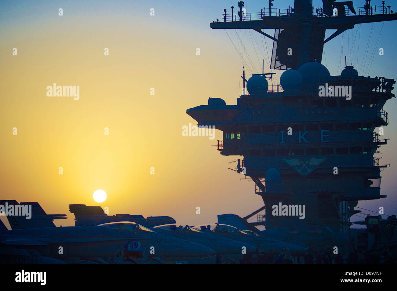 The Nimitz-class aircraft carrier USS Dwight D. Eisenhower (CVN 69) prepares for night operations as the sun sets. Stock Photo