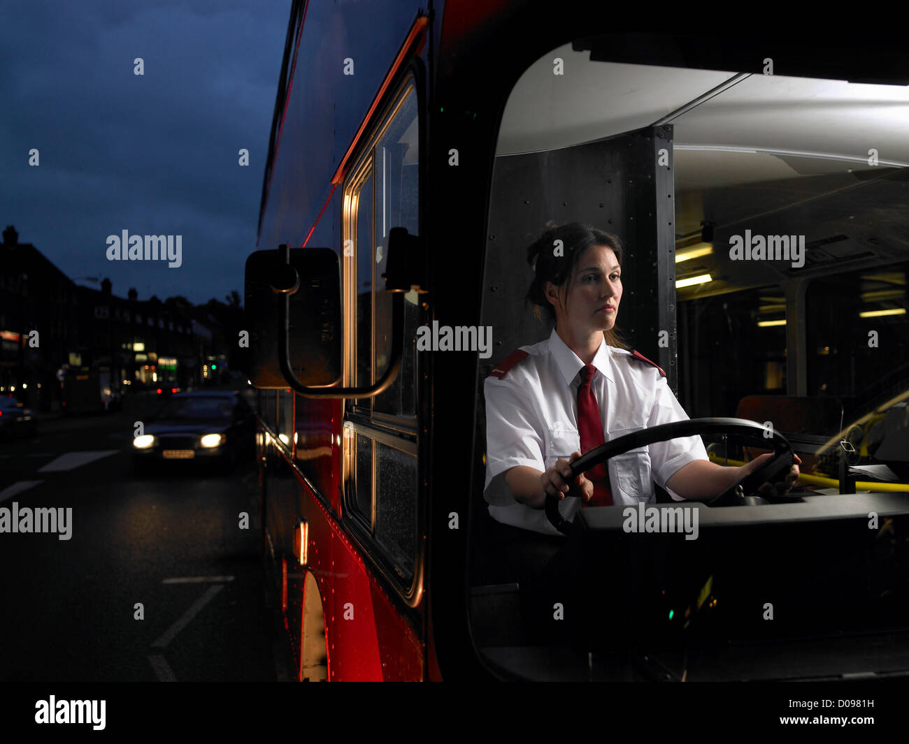 Female bus driver driving double decker bus through urban environment at night - Stock Image
