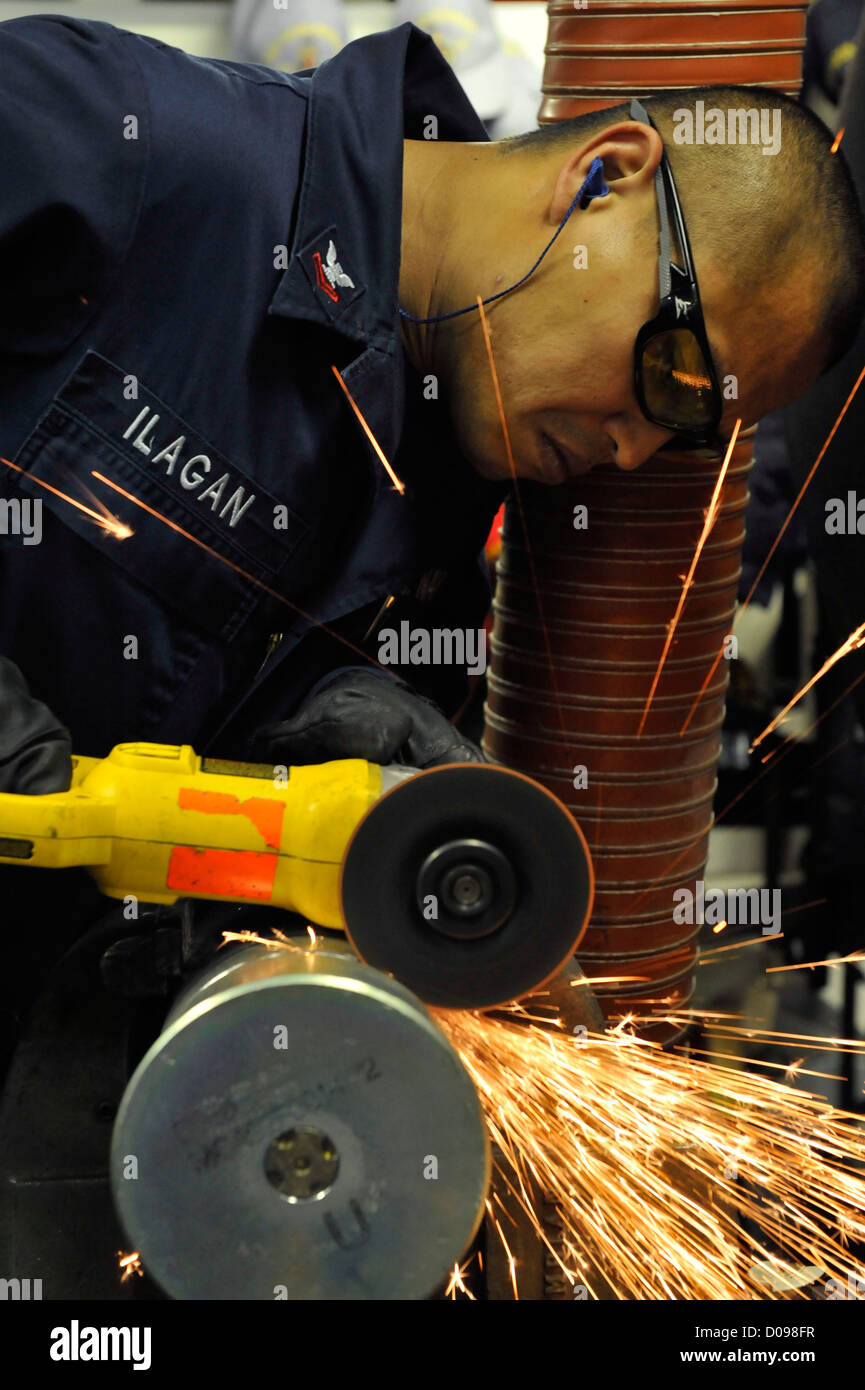 Machinery Repairman 2nd Class Erickson Ilagan, from New York, uses a grinder with a cutting disc to cut a MK 45 - Stock Image