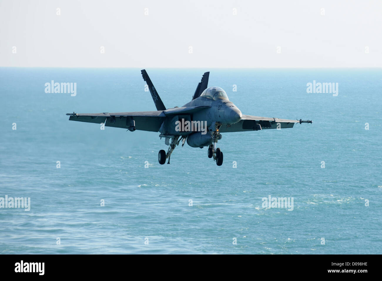 F/A-18F Super Hornet from the Jolly Rogers of Strike Fighter Squadron (VFA) 103 approaches the Nimitz-class aircraft carrier US Stock Photo