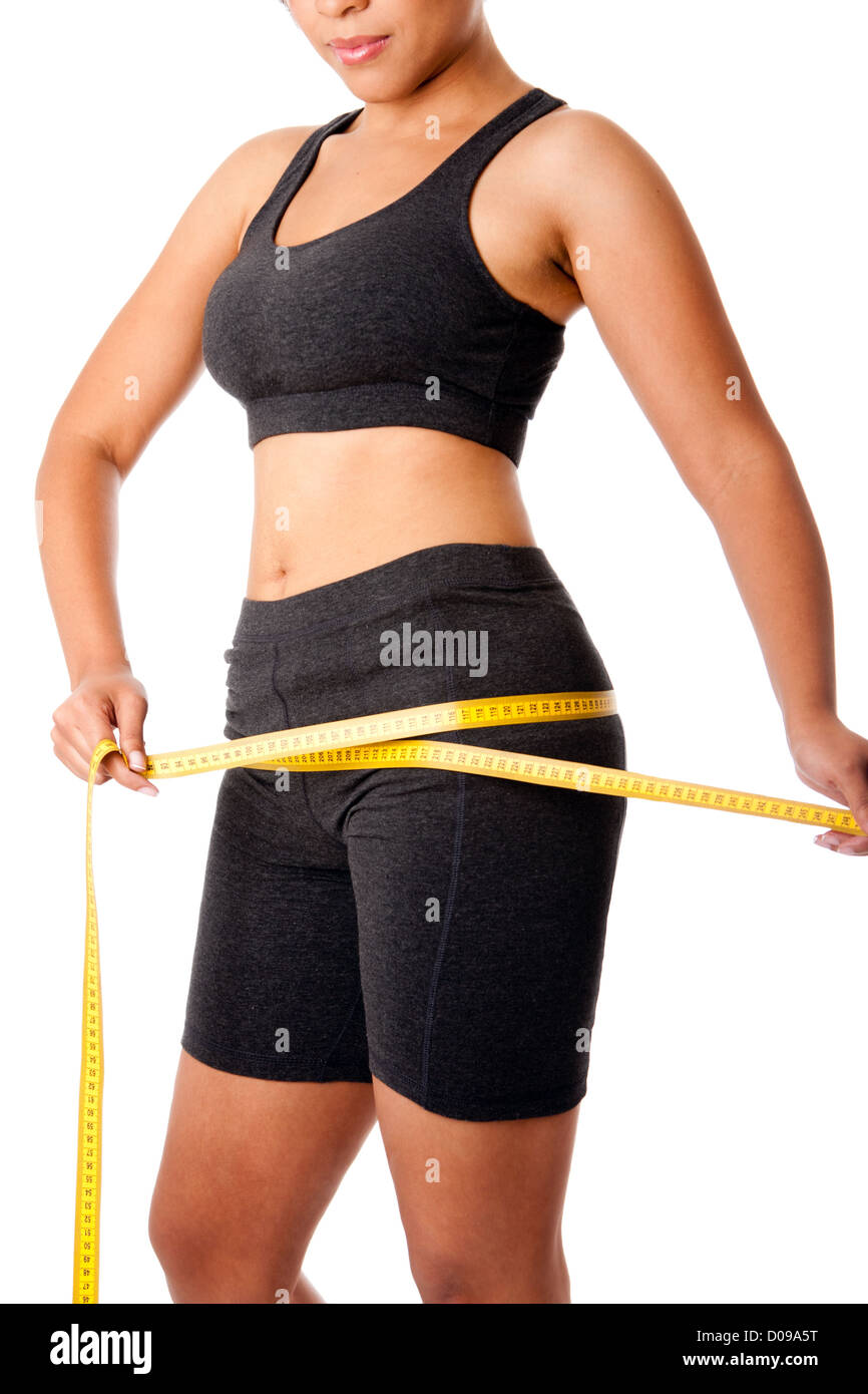 Woman dressed in grey measuring size of thigh, healthy lifestyles weightloss concept, isolated. - Stock Image