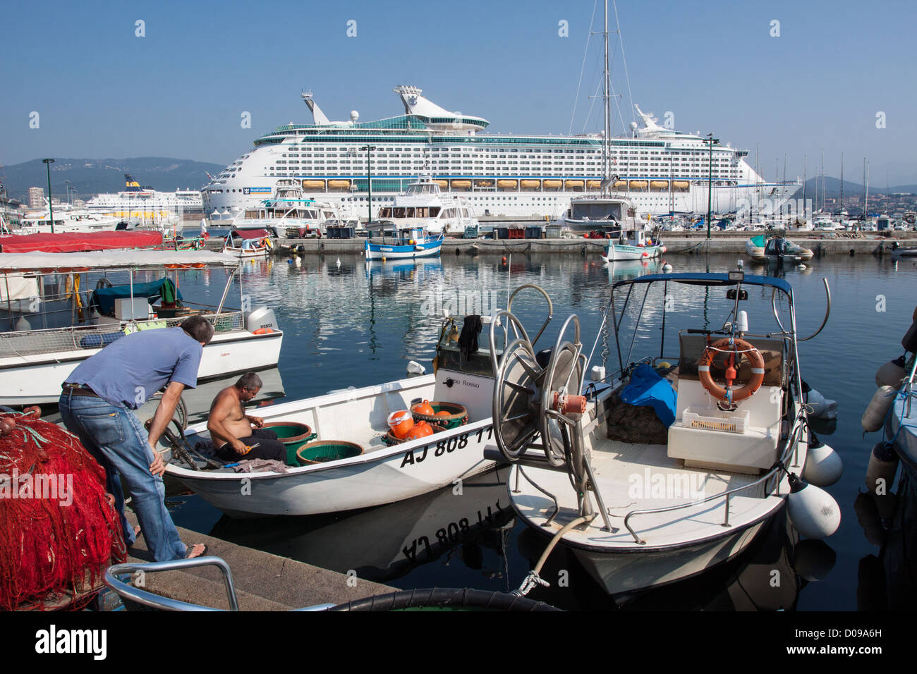 CONTRAST BETWEEN SMALL FISHING BOATS IMMENSE CRUISE SHIP FROM COMPANY ROYAL CARIBBEAN INTERNATIONAL PORT AJACCIO - Stock Image