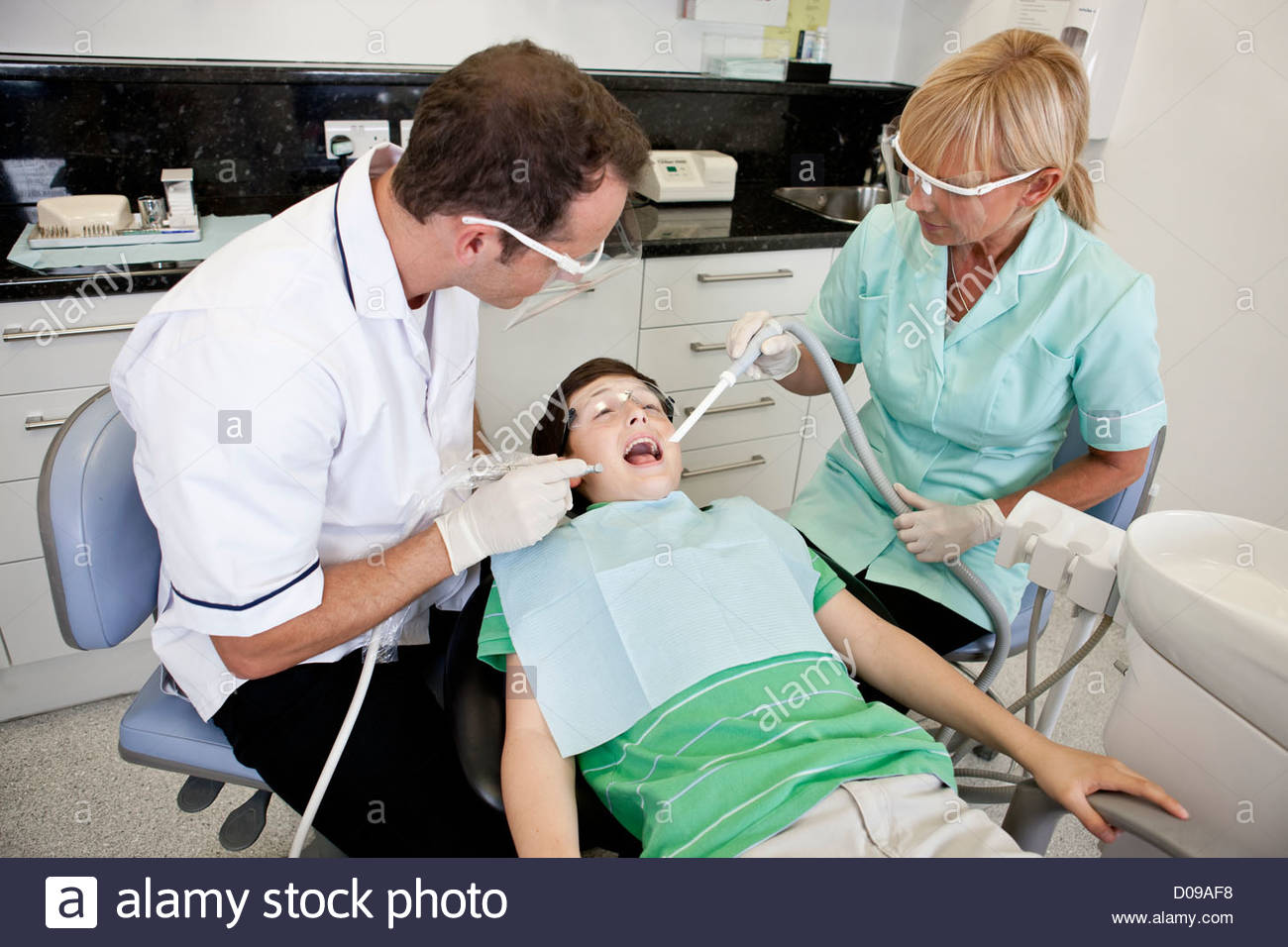 A young boy patient having dental treatment, looking scared - Stock Image