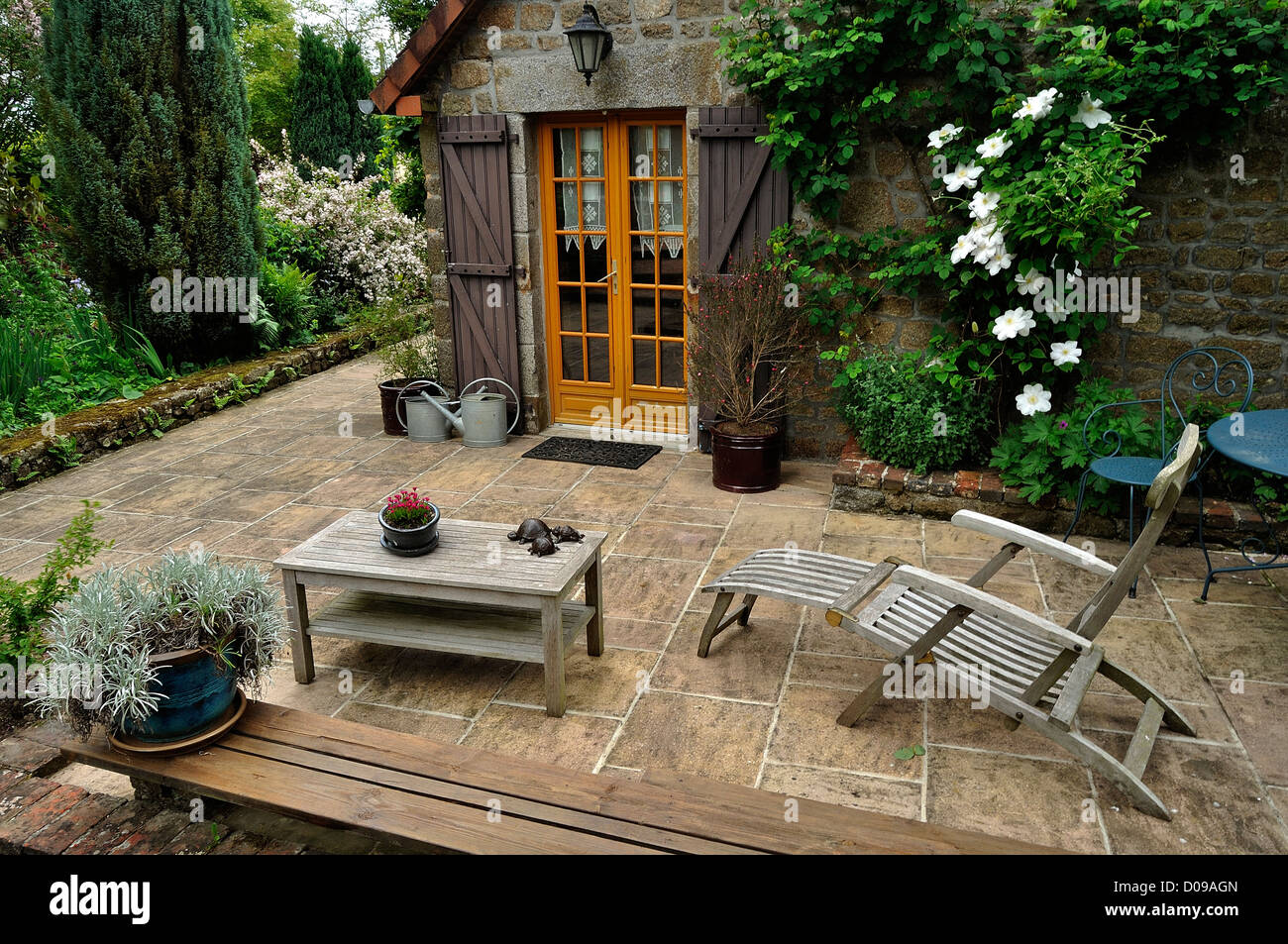 A terrace garden, furniture out of wooden, a clematis on the wall of ...