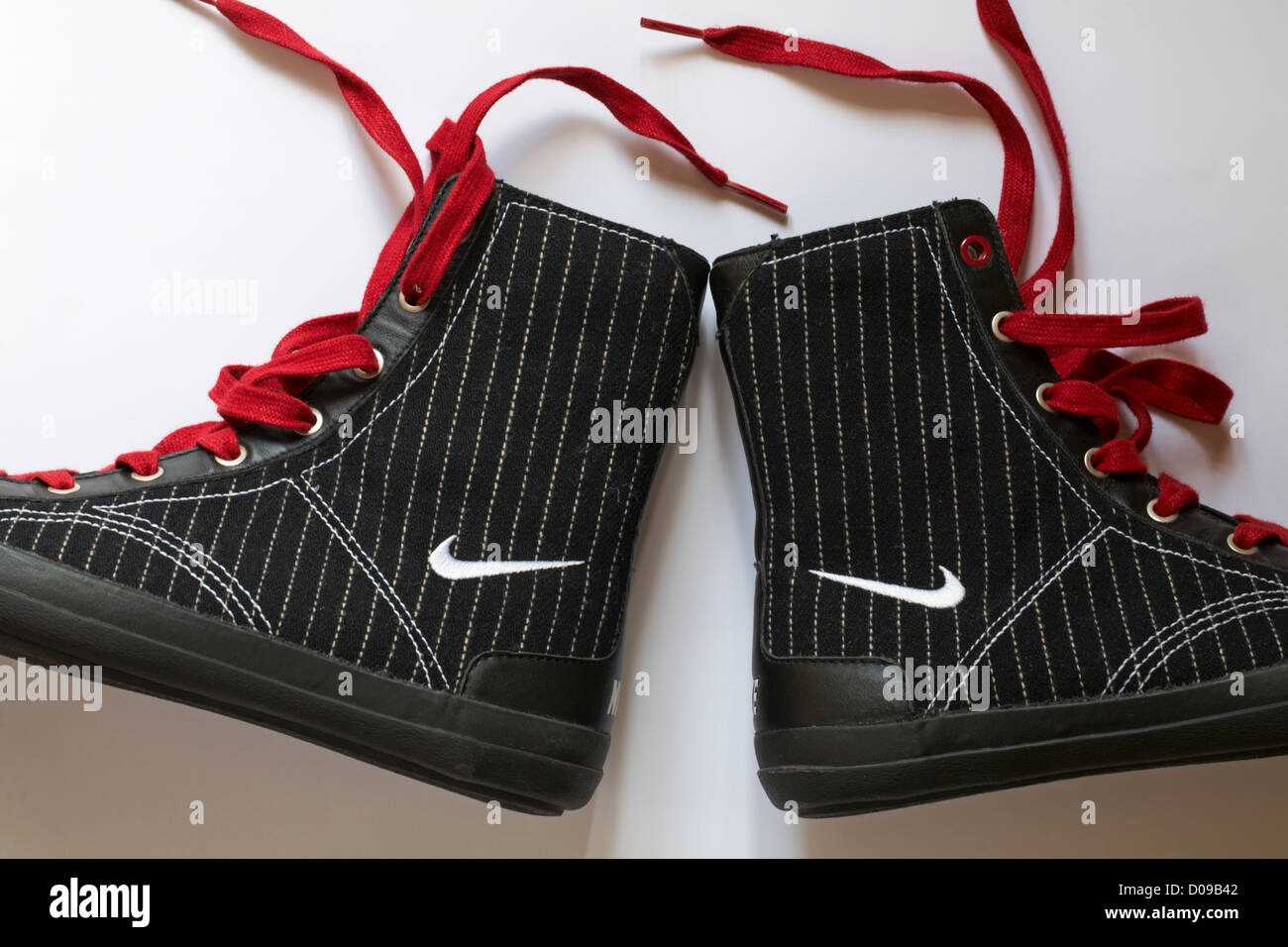3b3ec10839a4 Pair of boots with Nike logo and red laces set on white background - Stock  Image