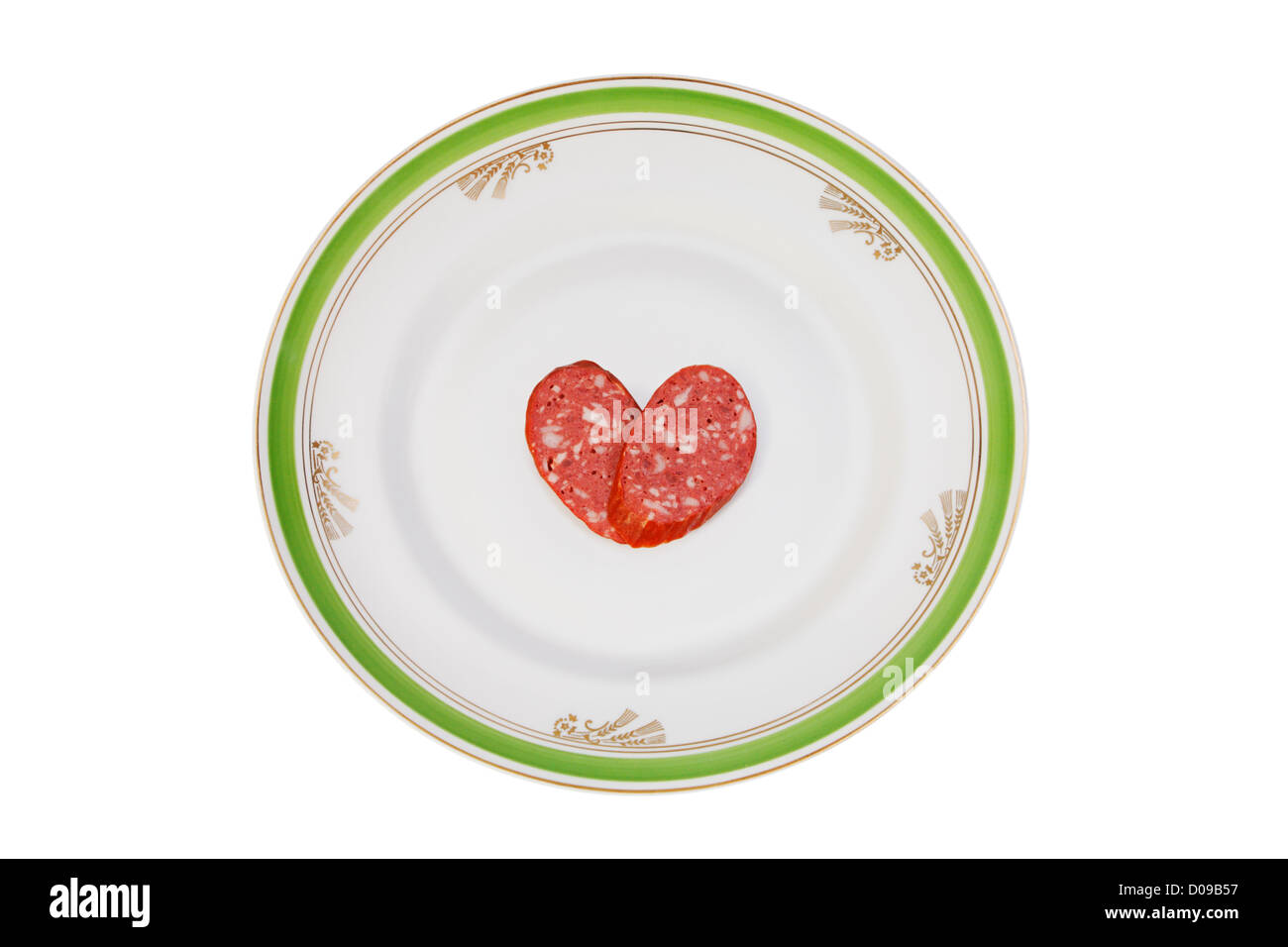 Slices of sausage in the form of a heart on a old dinner plate - Stock Image