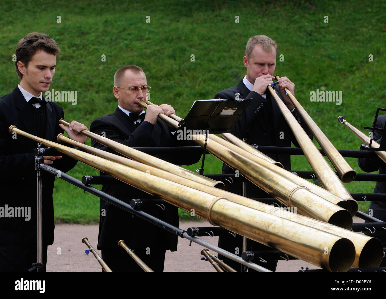 A band playing single tone brass horns entertains visitors at Peterhof. St Petersburg, Russia. - Stock Image