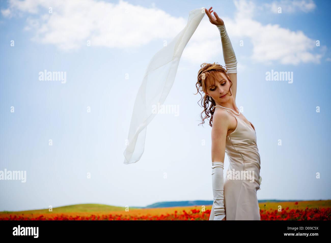 Woman posing over blu sky background in poppy field - Stock Image