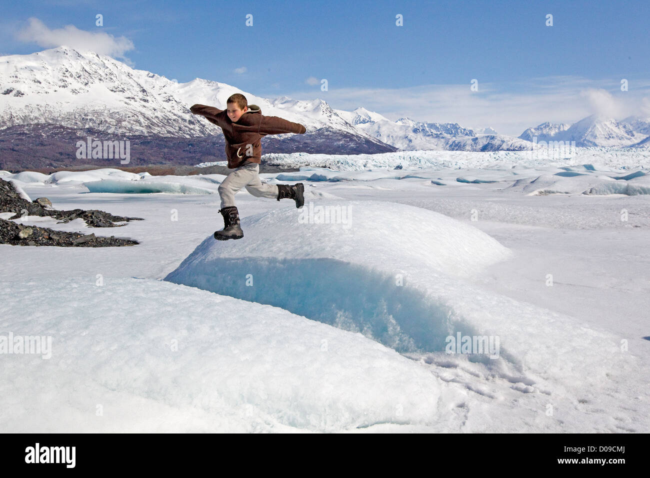 Boy leaps on Alaska glacier, Alaskan wilderness, Chugach Mountains, Alaska, US - Stock Image
