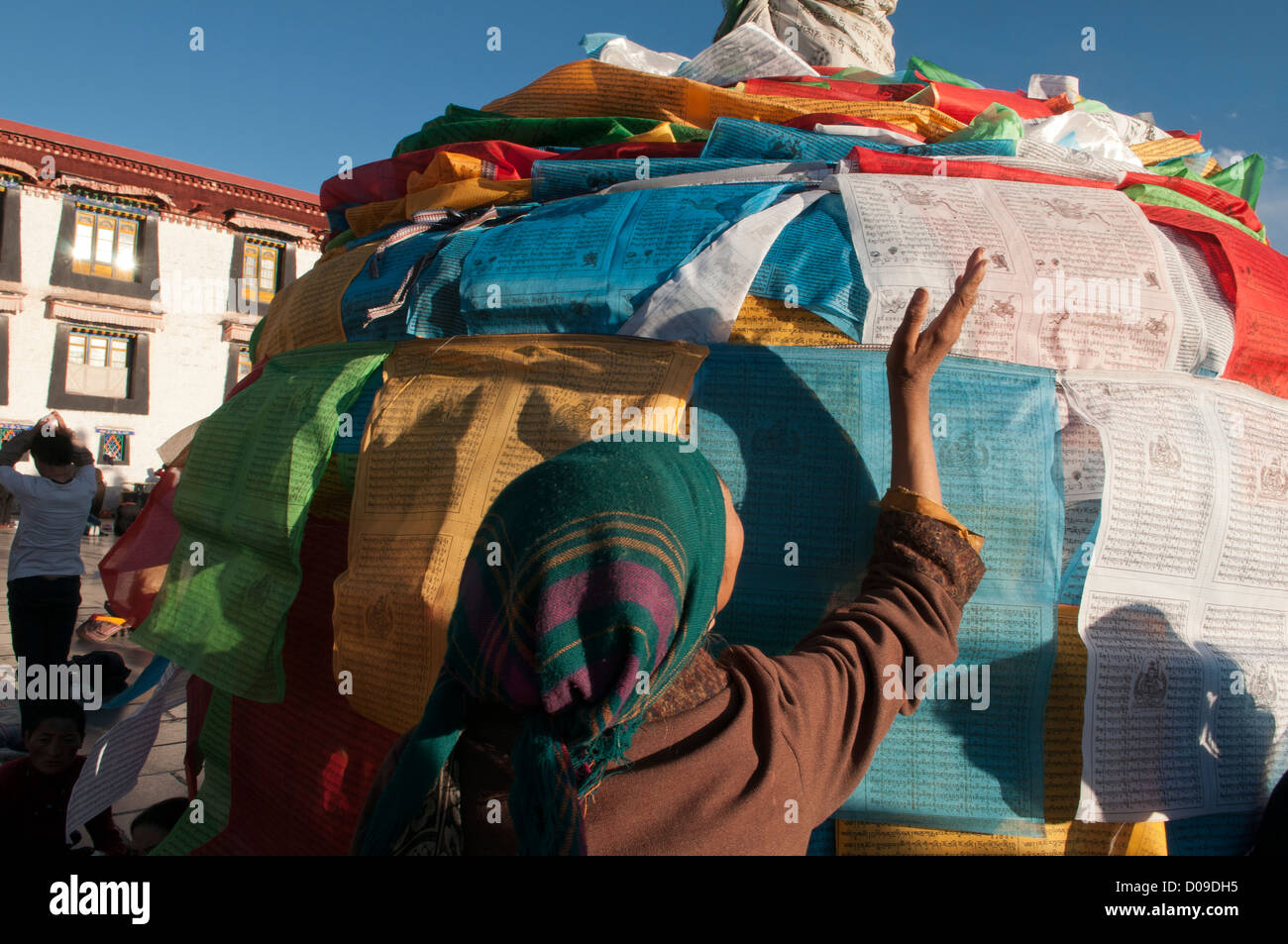Prayer flags cover pagoda as pilgrims pray at Jokhang Temple on Barkhor Square at sunset, Lhasa, Tibet, China - Stock Image
