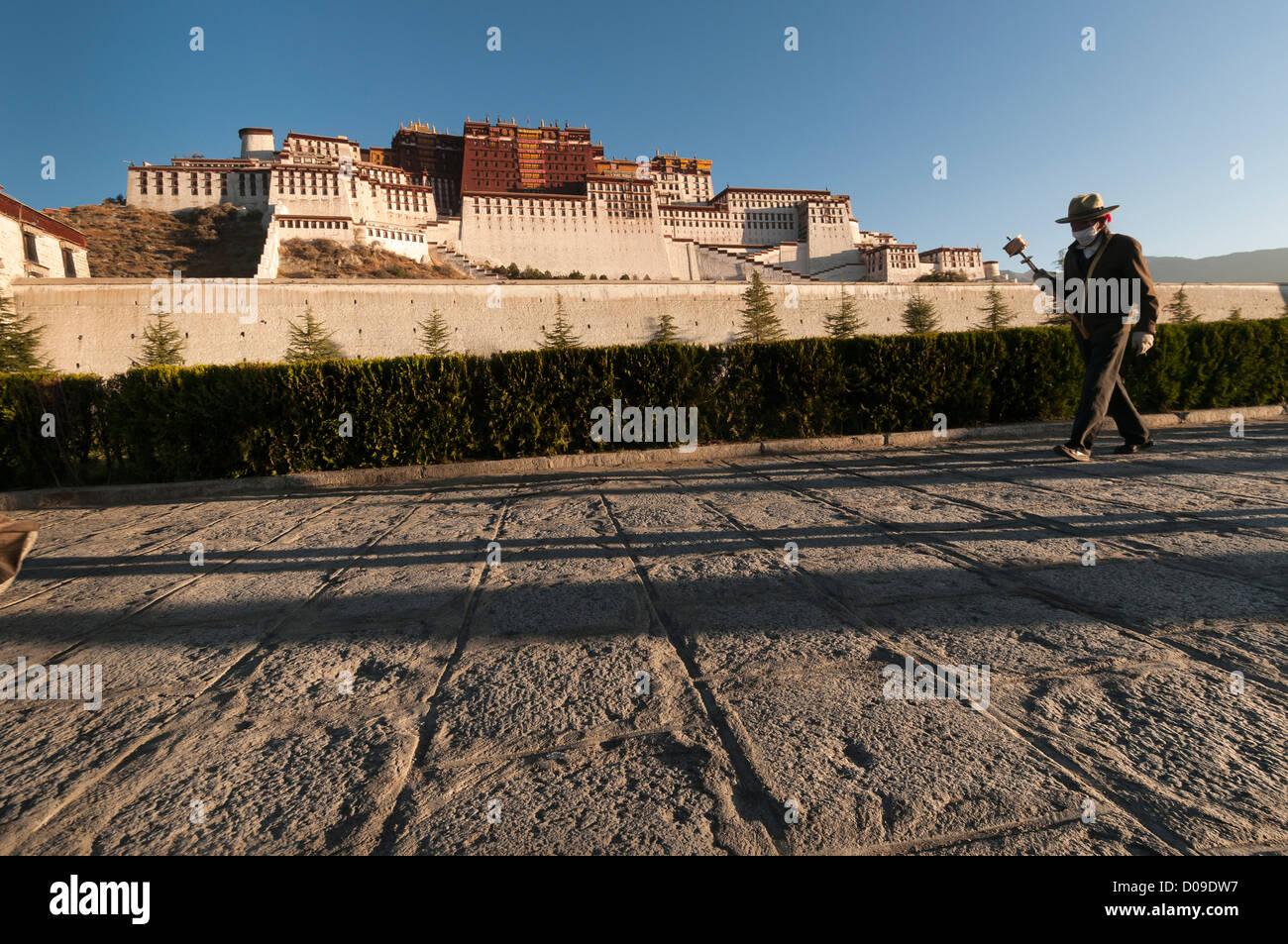 Tibetan Buddhist pilgrim carrying prayer wheel walks around Portala Palace at dawn, Lhasa, Tibet, China - Stock Image