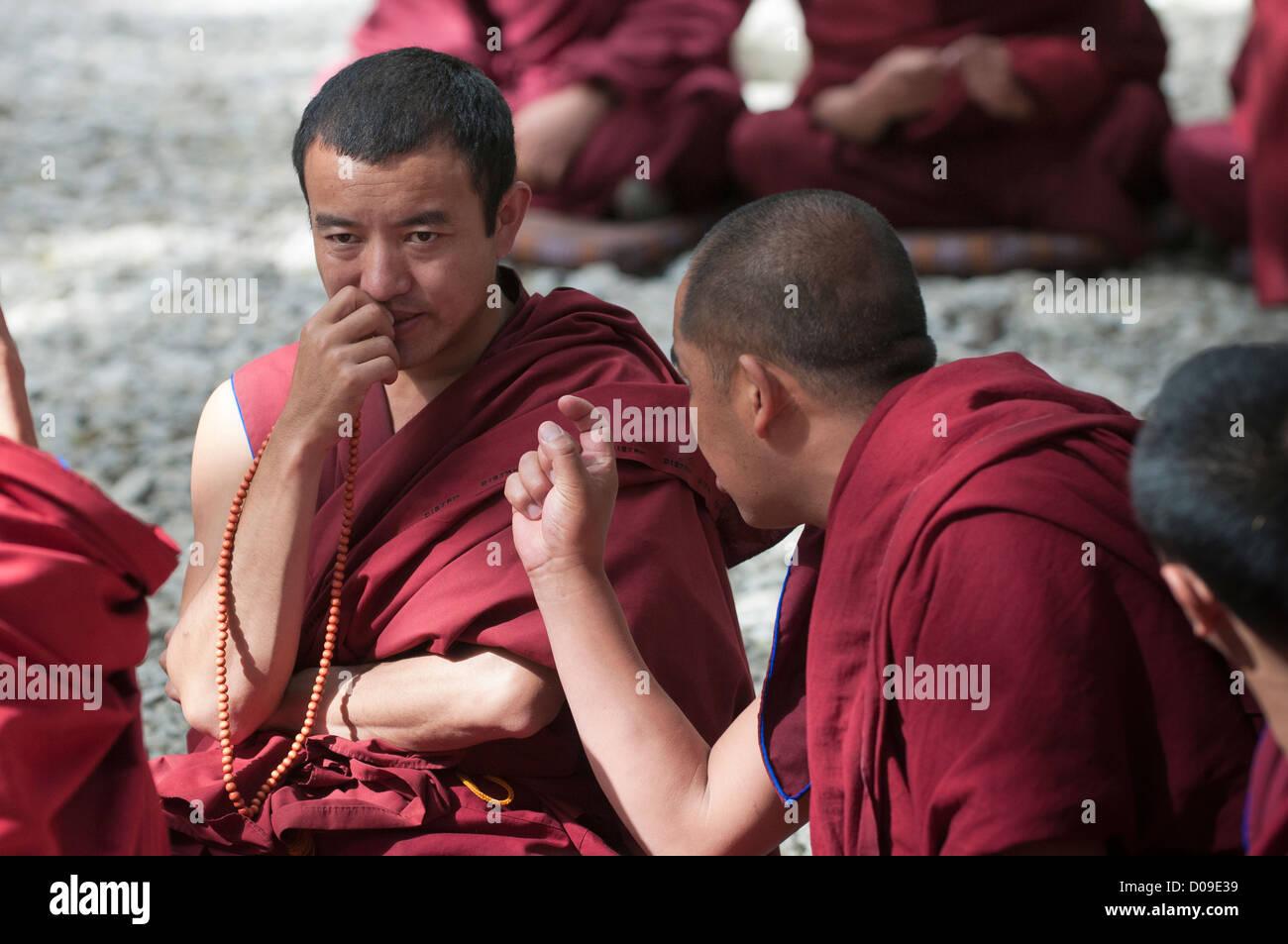 Buddhist monk makes point during debate as partner considers, Drepung Monastery, Lhasa, Tibet, China - Stock Image