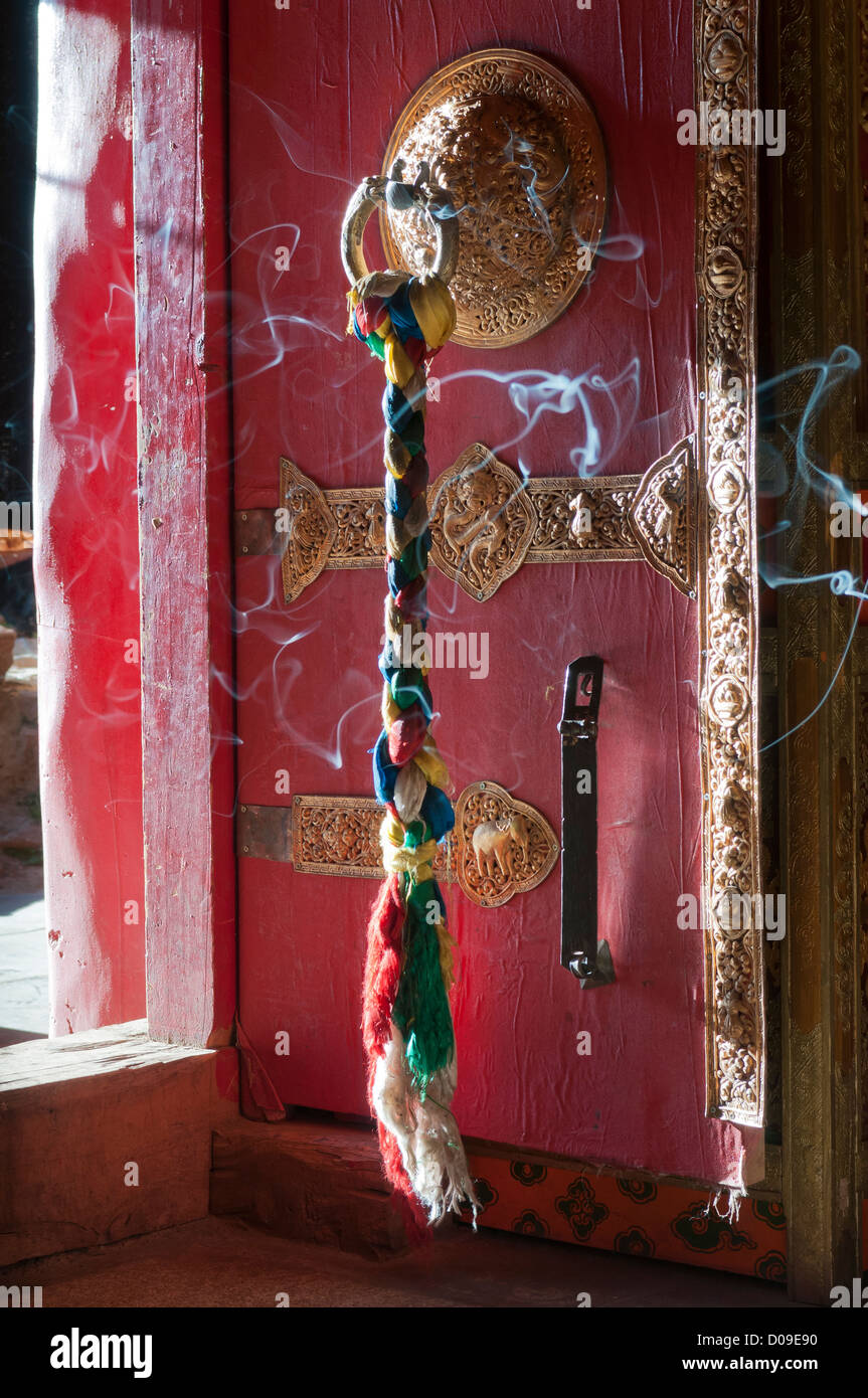 Incense wafts past ornate door that guards entrance to temple, Reting Monastery, Tibet, China - Stock Image