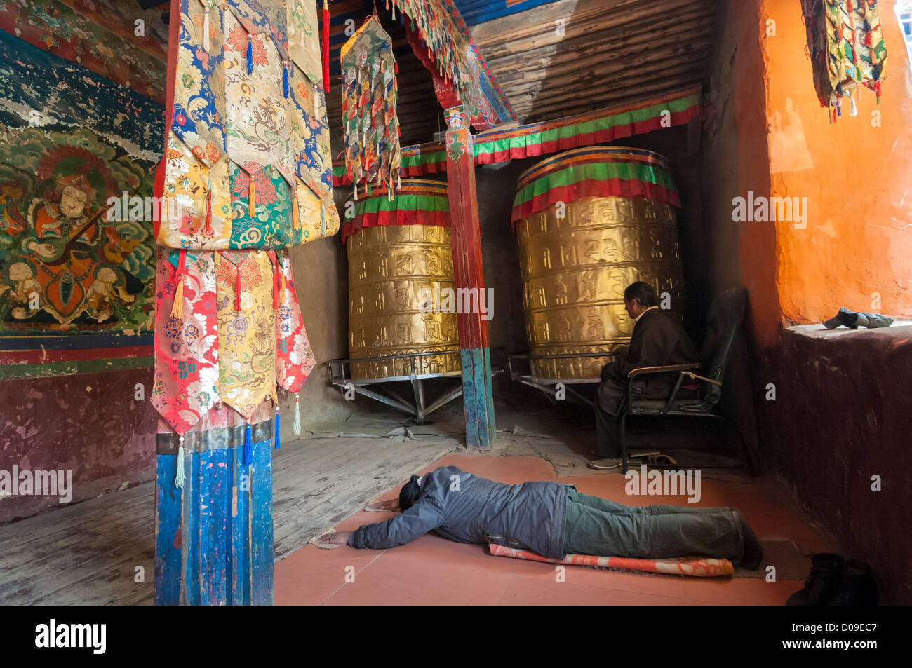 Pilgrim prays at entrance to temple of Drigung Terdrom Nunnery, Tibet, China - Stock Image