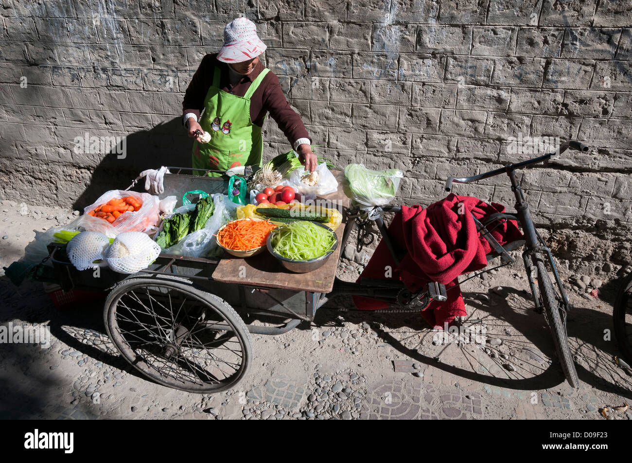 Woman sells fresh vegitables from bicycle card in dusty alley, Lhasa, Tibet - Stock Image