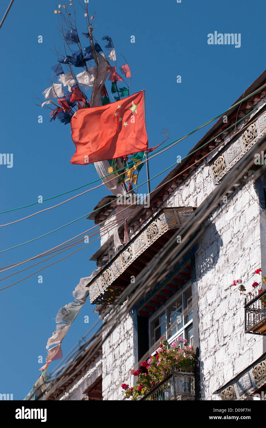 Chinese flag shares rooftop with traditional Buddhist prayer flags near Barkhor Square, Lhasa, Tibet, China - Stock Image