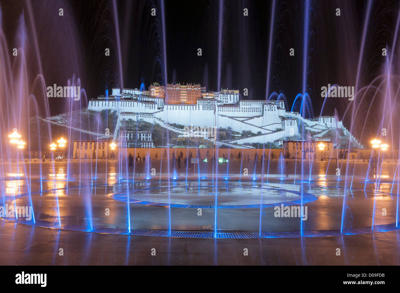 Fountains dance to music during light show at Chinese-bulit plaza below Portala Palace, Lhasa, Tibet, China - Stock Image
