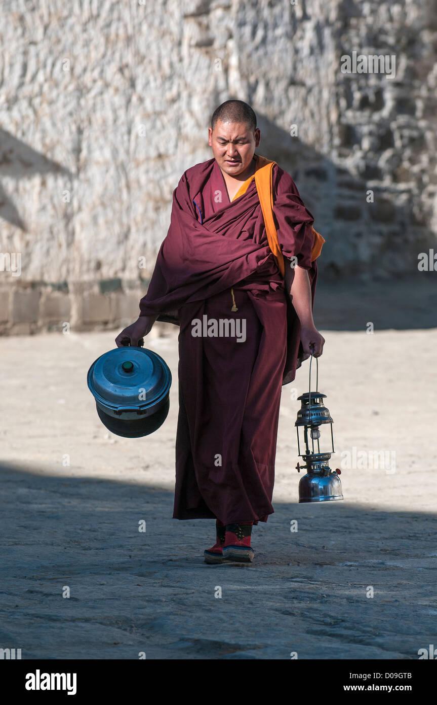 Early morning chores occupy Buddhist monk, Tashilhunpo Monastery, Shigatse, Tibet, China - Stock Image
