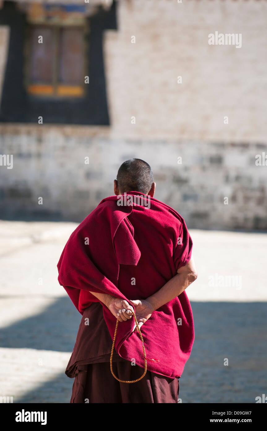 Buddhist monk takes contemplative walk at Tashilhunpo Monastery, Shigatse, Tibet, China - Stock Image