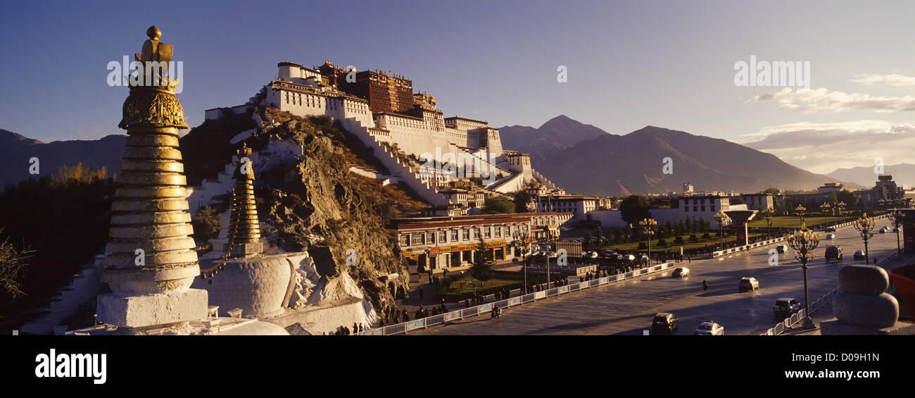 Pilgrims and vehicle traffic pass Portala Palace at sunrise, Lhasa, Tibet, China. - Stock Image
