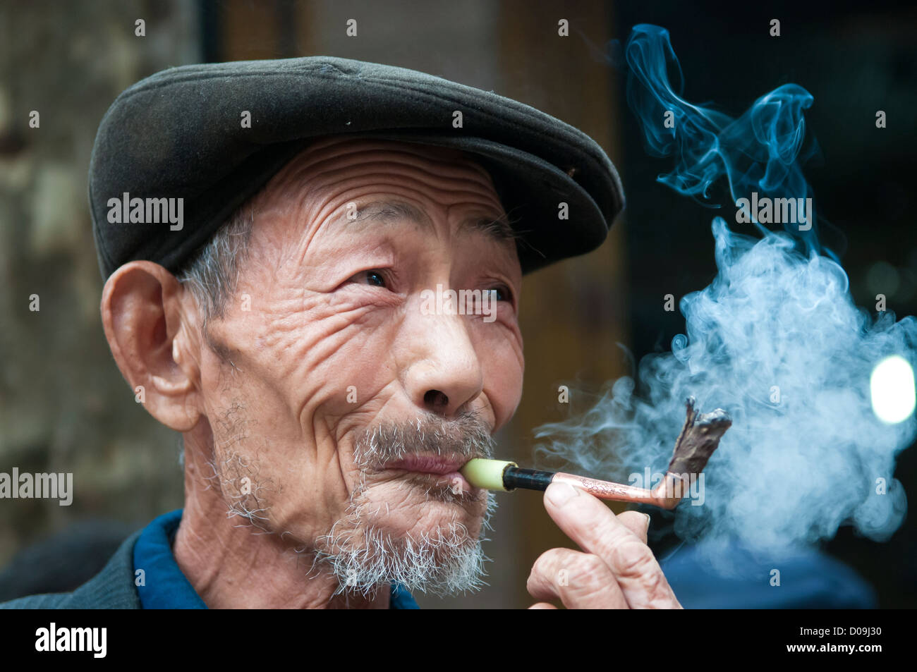 e22a68f5f Man smokes pipe while chatting with friends on market day in village on  outskirts of Chengdu
