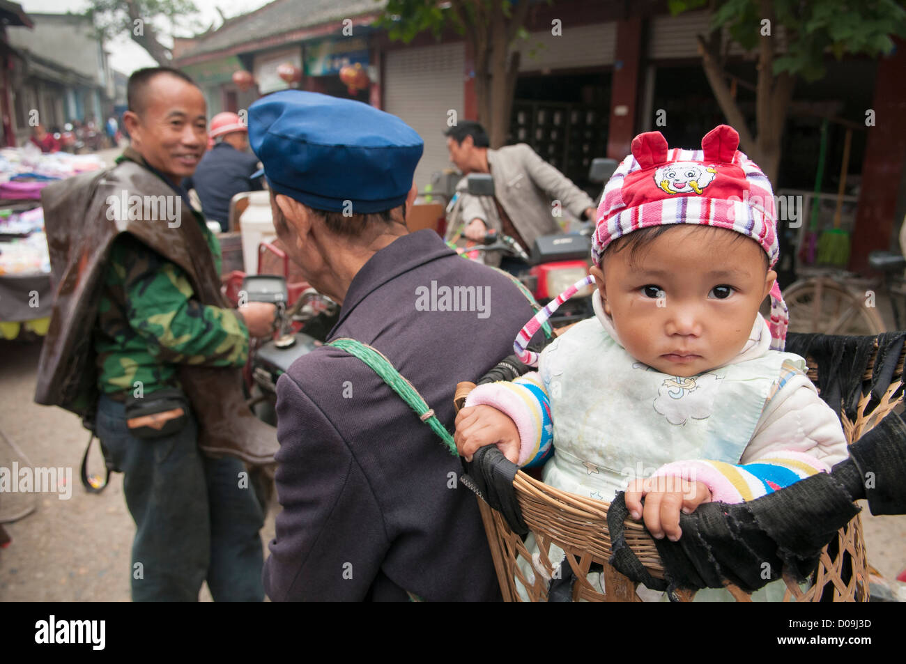 Baby boy is carried in basket by grandfather on busy market day in village on outskirts of Chengdu, Sichuan Province, - Stock Image