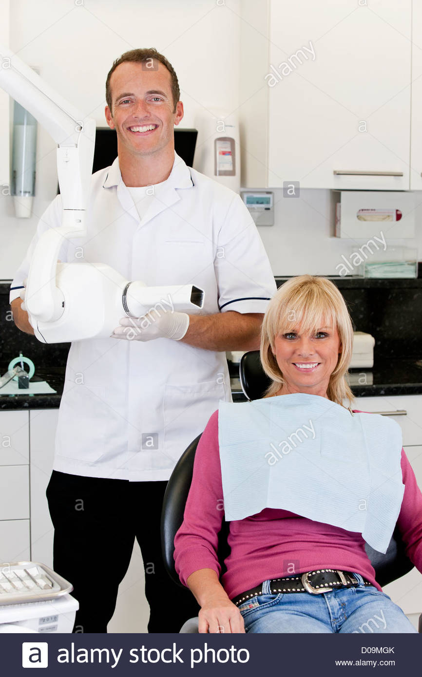 A male dentist with a female patient in his surgery Stock Photo