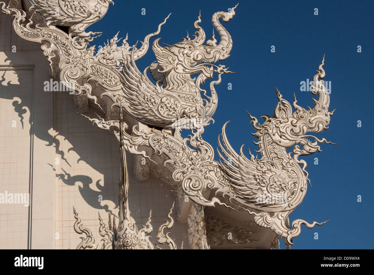 Chalermchai Kositpipat dragons adorning roof white temple or wat rong khun temple built