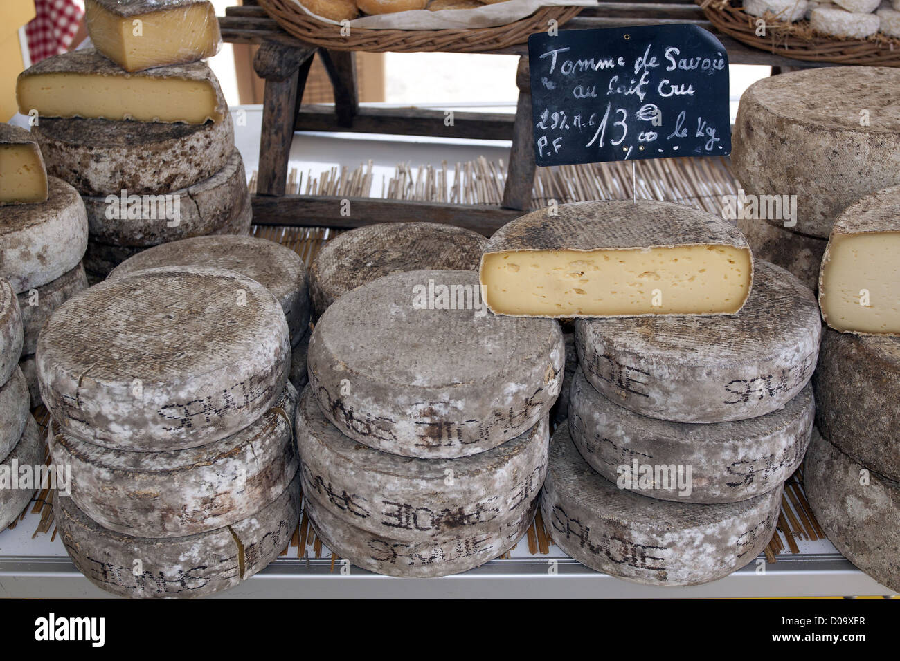 TOMMES DE SAVOIE CHEESES ON SALE ON A CHEESE-MAKER'S STALL IN THE MARKET OF ALLEVARD ISERE RHONE-ALPES FRANCE Stock Photo