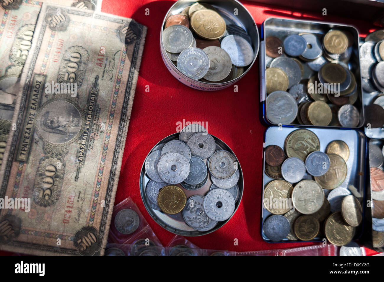 Old Greek drachma coins and bank notes for sale during Saturday antique bazaar in Bit Bazaar antiques street market - Stock Image