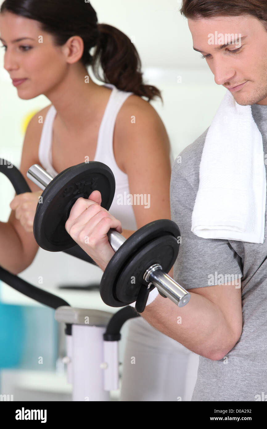 Young people working out in a gym - Stock Image
