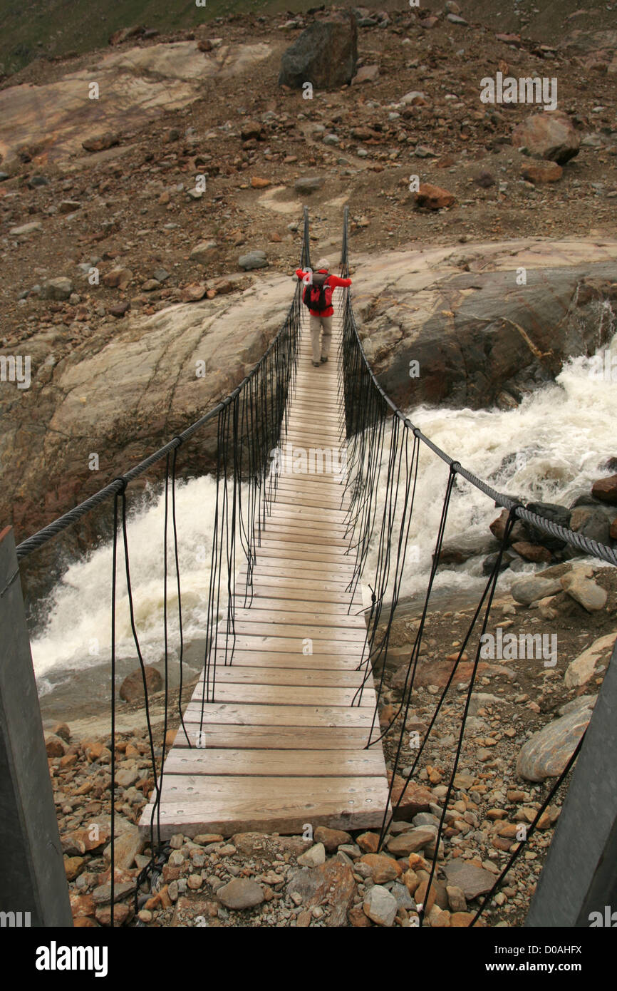 walk on hanging Himalayan style bridge over melt stream from Forni glacier, upper Valfurva, Lombardy, Italy - Stock Image