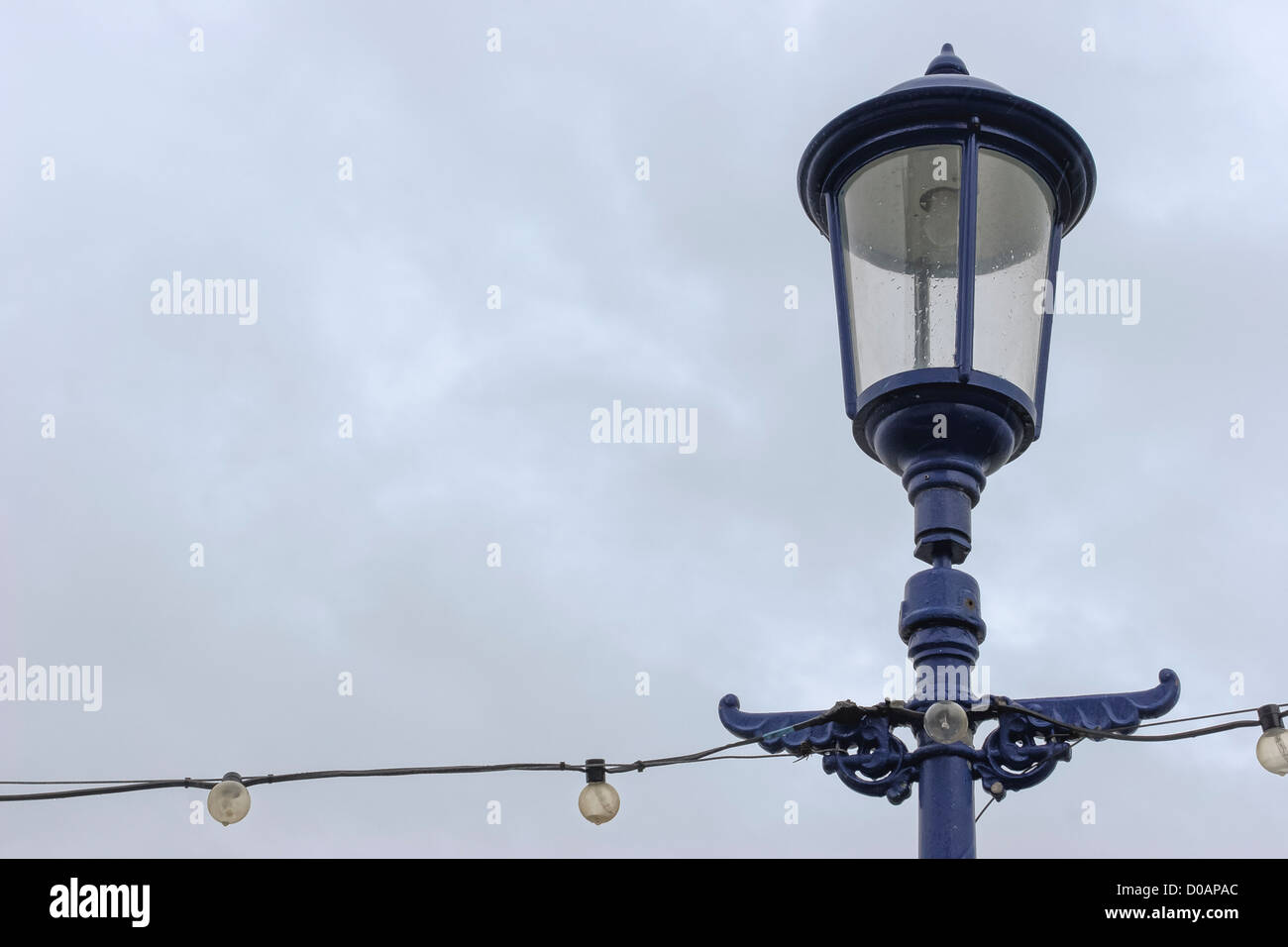 Street Lamp Set in Front of an Overcast Sky on Eastborne Pier - Stock Image