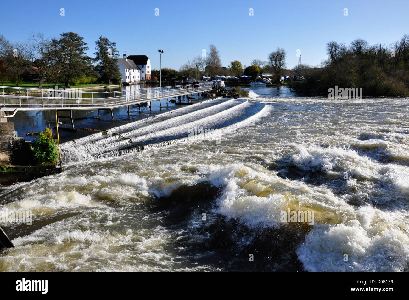 Bucks - Hambleden Mill End - surging water over the Thames weir - creating a rough white water tail - bright winter - Stock Image