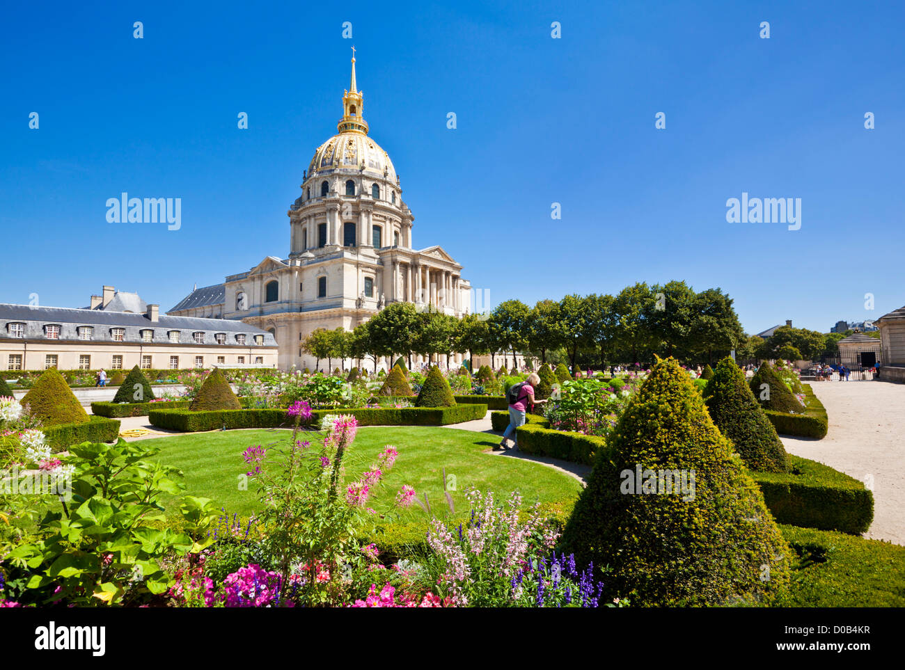 Person looking at the flowers in the gardens of the Eglise du Dome Les Invalides napoleons tomb Paris France EU - Stock Image