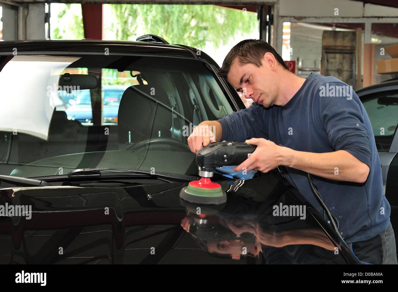 Polishing a black bonnet. - Stock Image