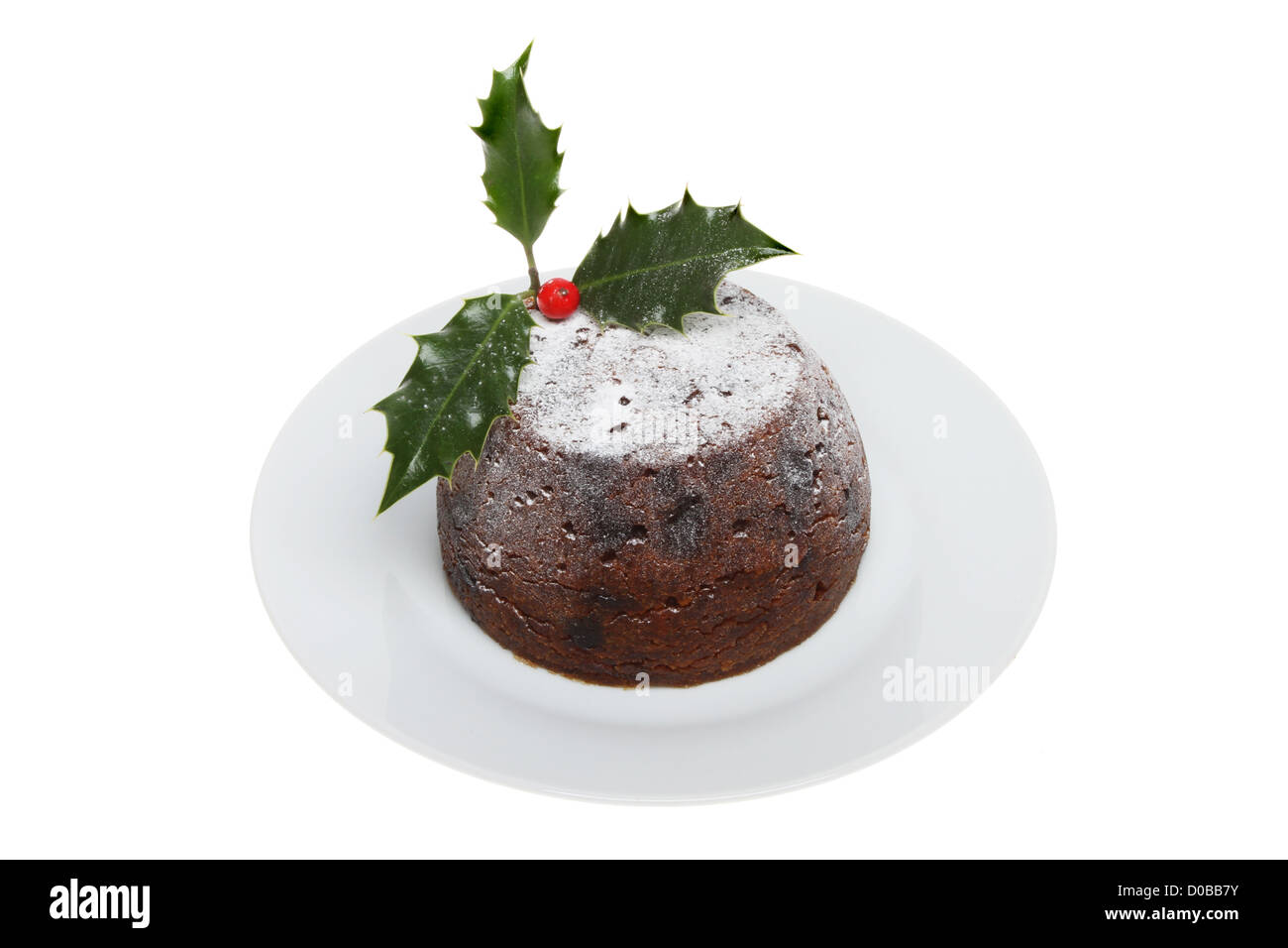 Christmas pudding on a plate decorated with holly and dusted with icing sugar isolated against white - Stock Image