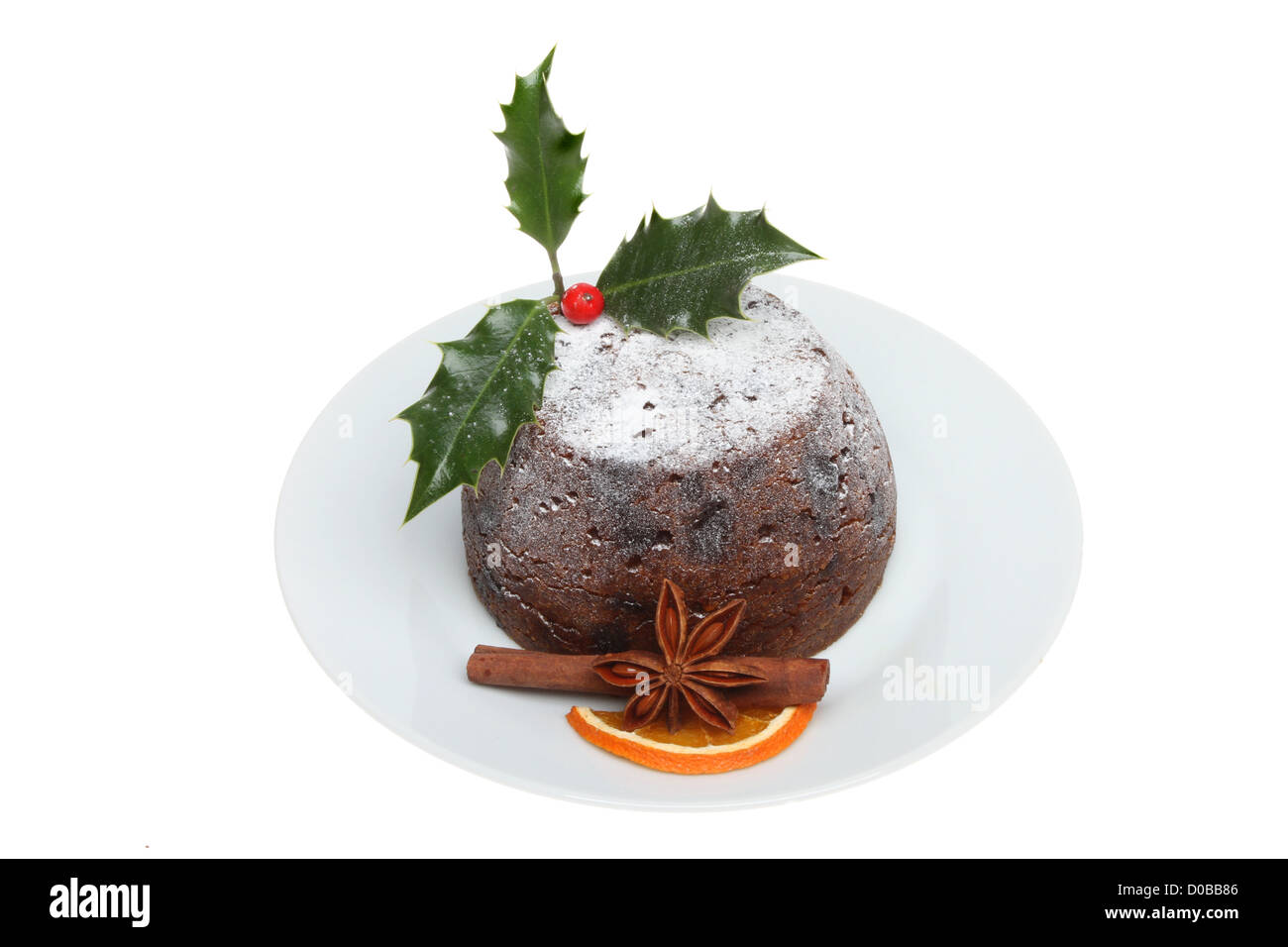 Christmas pudding on a plate decorated with holly and spices isolated against white - Stock Image