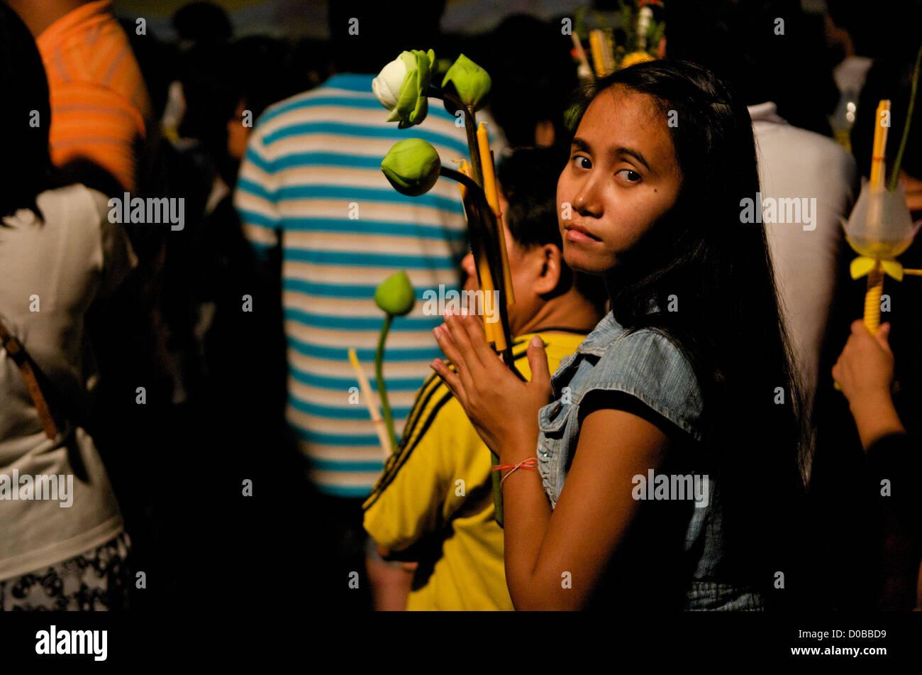 young Thai woman prays w/ candle, incense & Lotus flowers, Wat Saket, Phu Khao Thong (Golden Mountain), Bangkok, - Stock Image