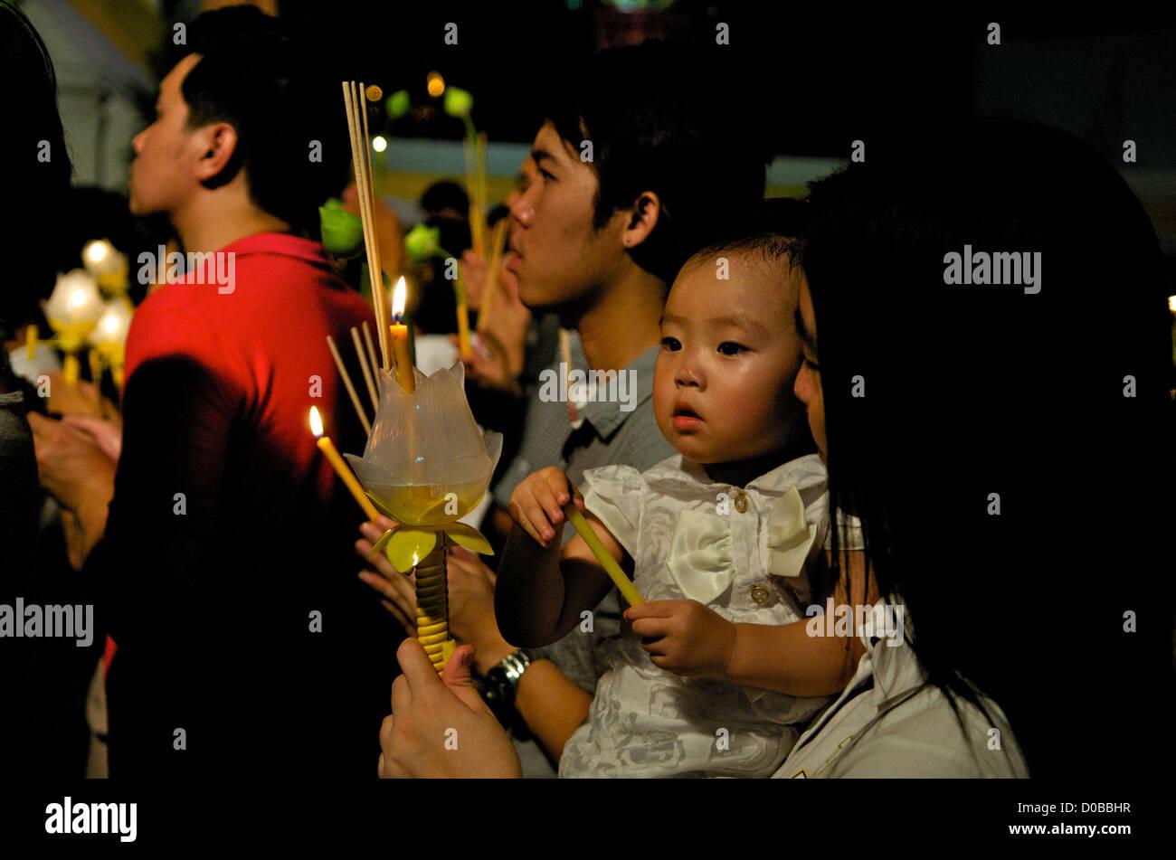 Thai family prays w/ candles & incense, Wat Saket, Phu Khao Thong (Golden Mountain), Bangkok, Thailand. credit: - Stock Image
