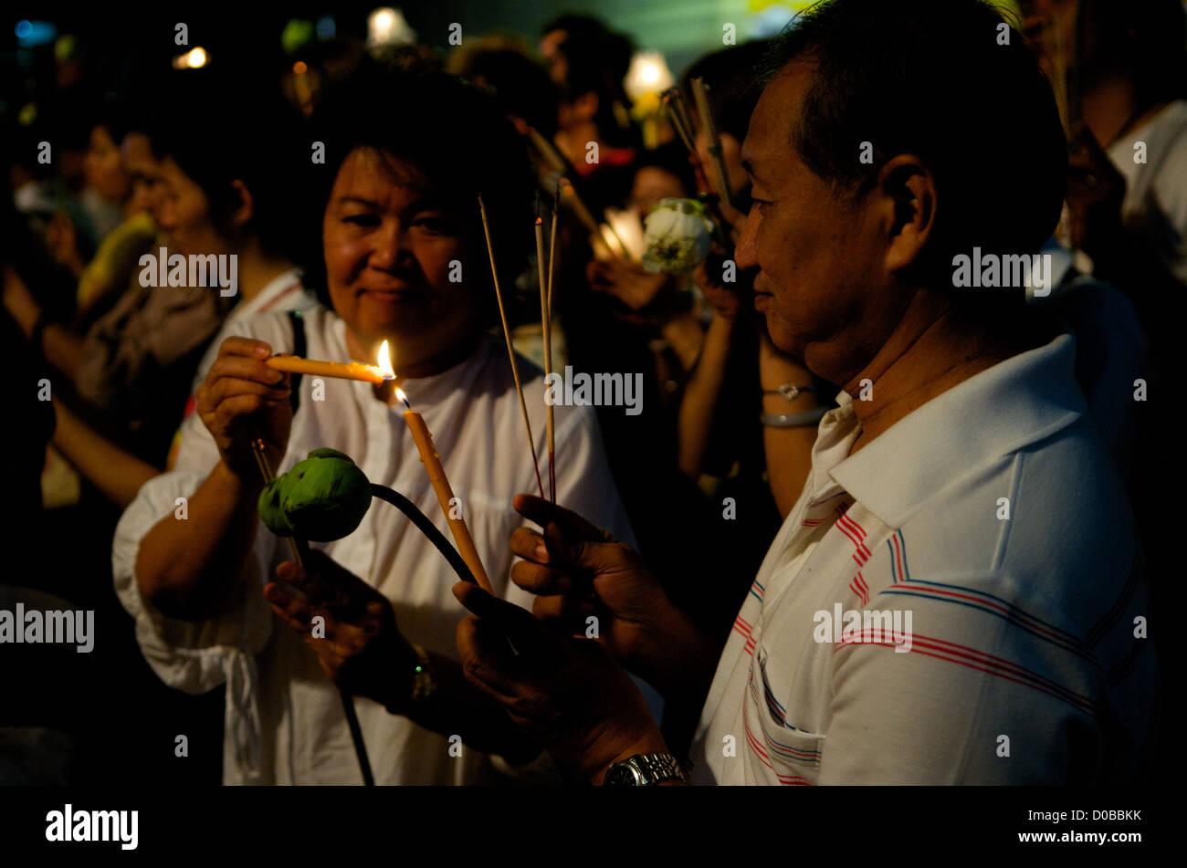 older Thai couple prays w/ candle, incense & Lotus flowers, Wat Saket, Phu Khao Thong (Golden Mountain), Bangkok, - Stock Image
