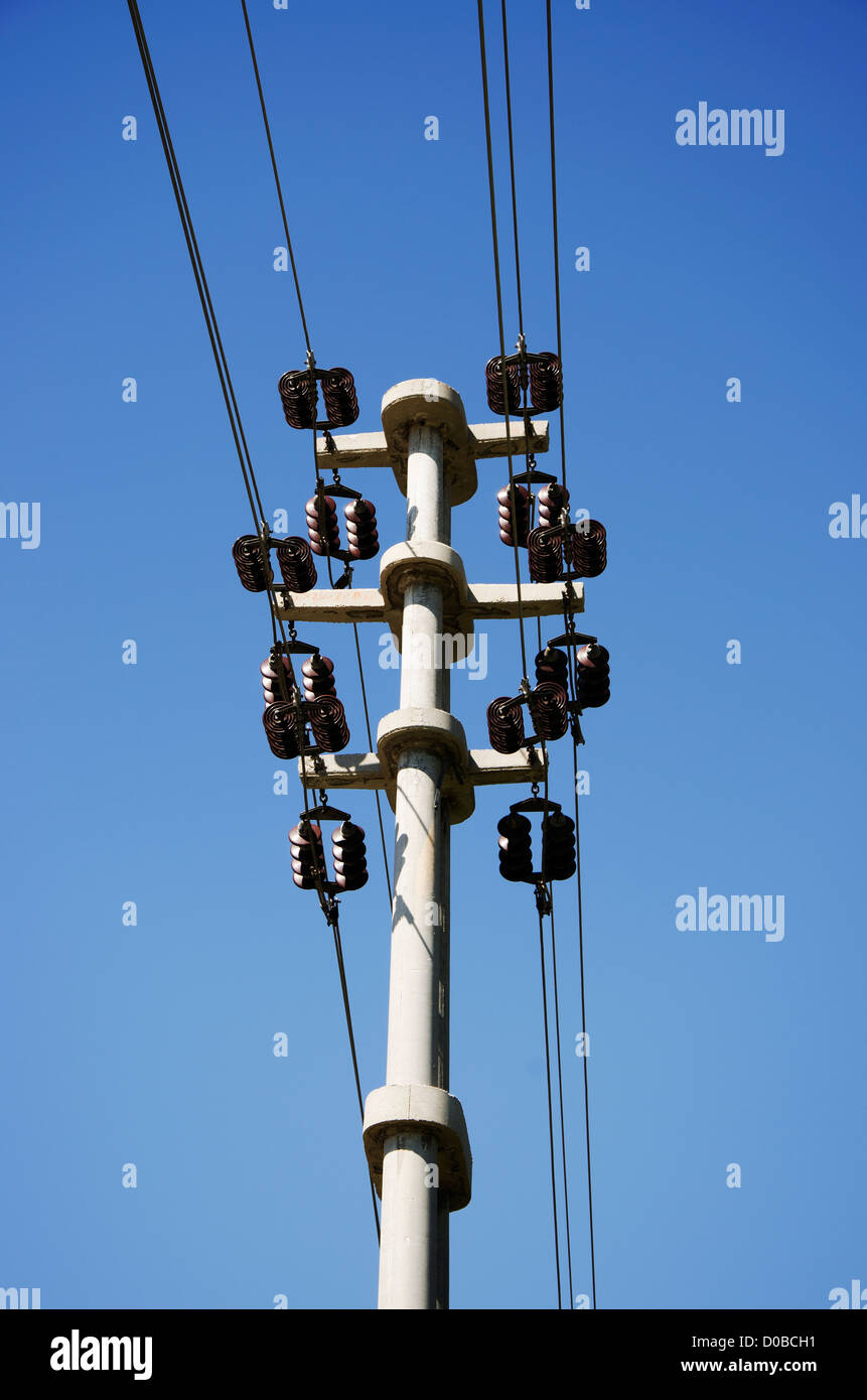 Transformers of an electrical post with powerlines against bright blue sky. - Stock Image