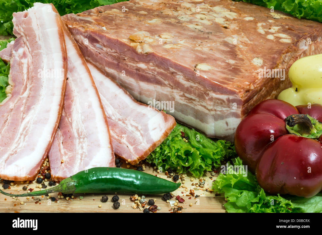 Still life with sliced romanian bacon and vegetables - Stock Image