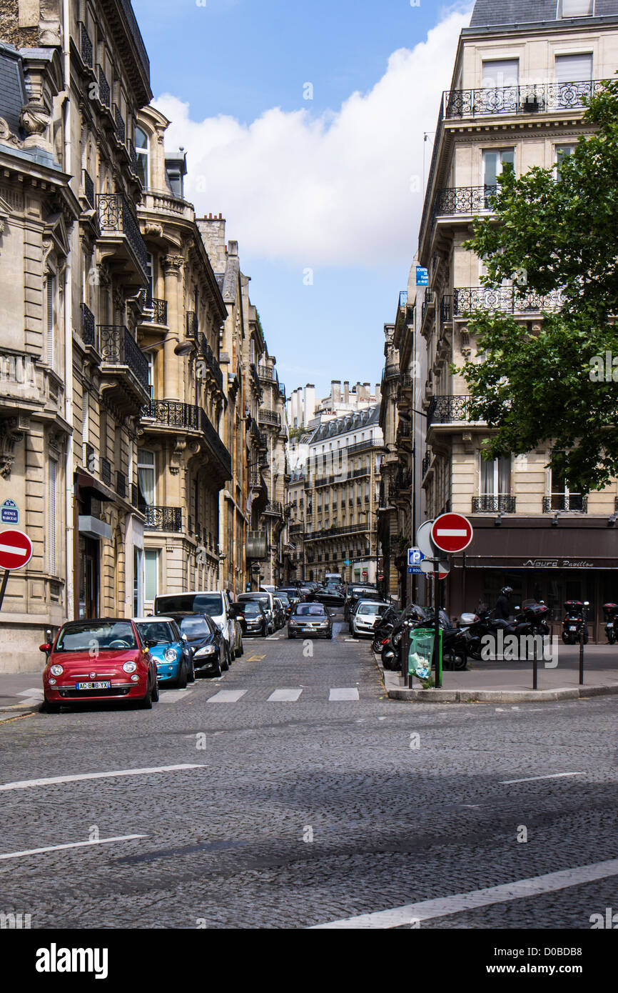Paris street scene corner of Avenue Marceau and Rue Jean Giraudoux with cars buildings and cobble stone street. - Stock Image