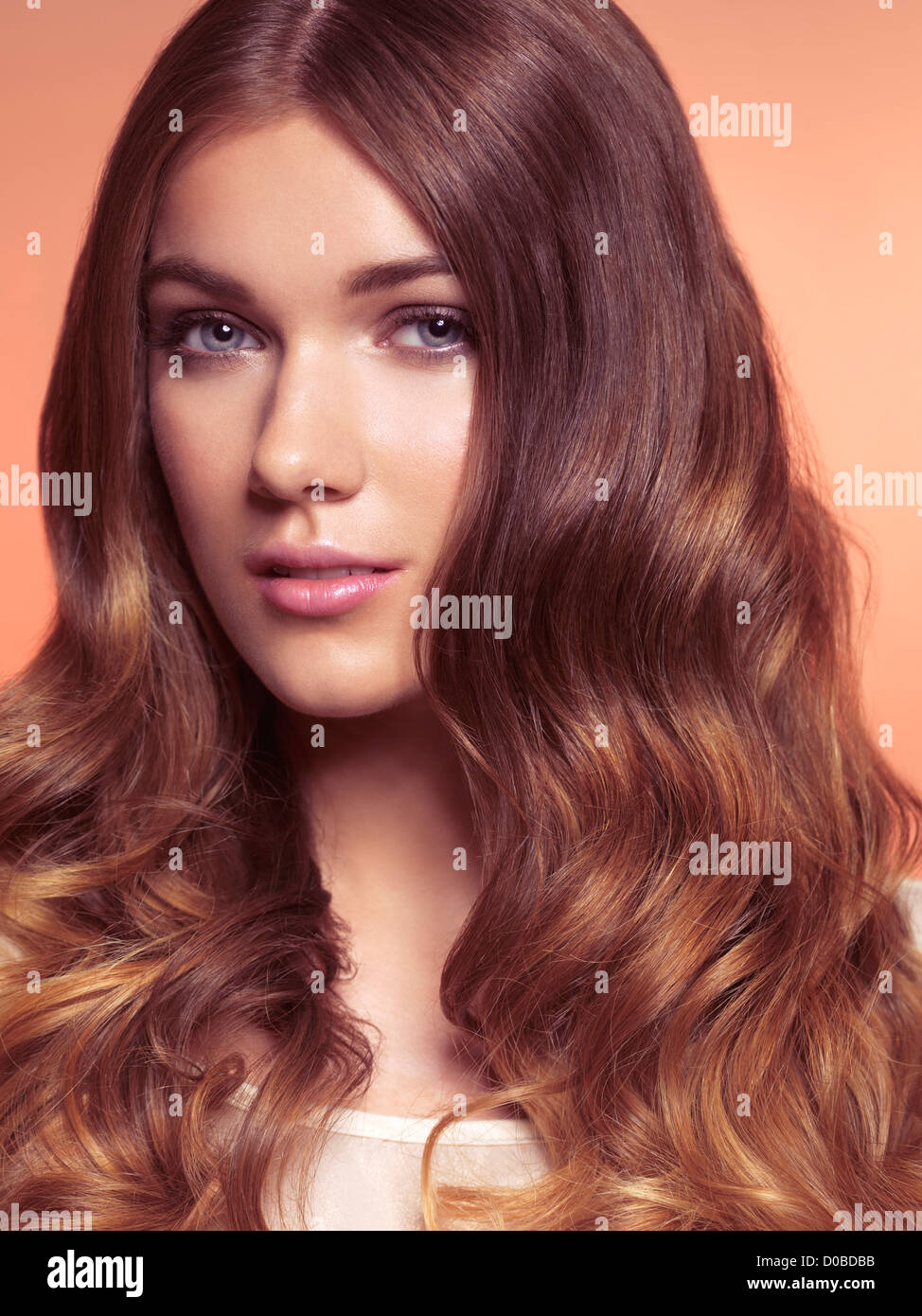 Beauty portrait of a young woman with long wavy brown hair - Stock Image