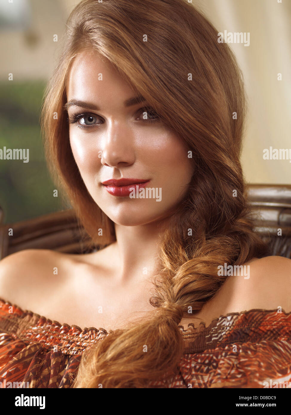 Beauty portrait of a young woman with long hair in a braid sitting in a chair - Stock Image
