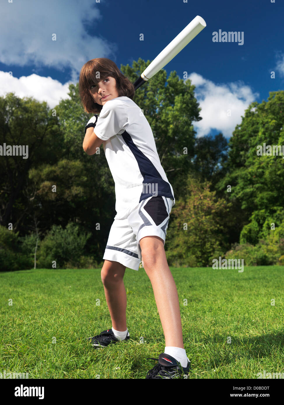 Action portrait of a ten year old boy with baseball bat practicing the game. Sports and children active lifestyle. - Stock Image