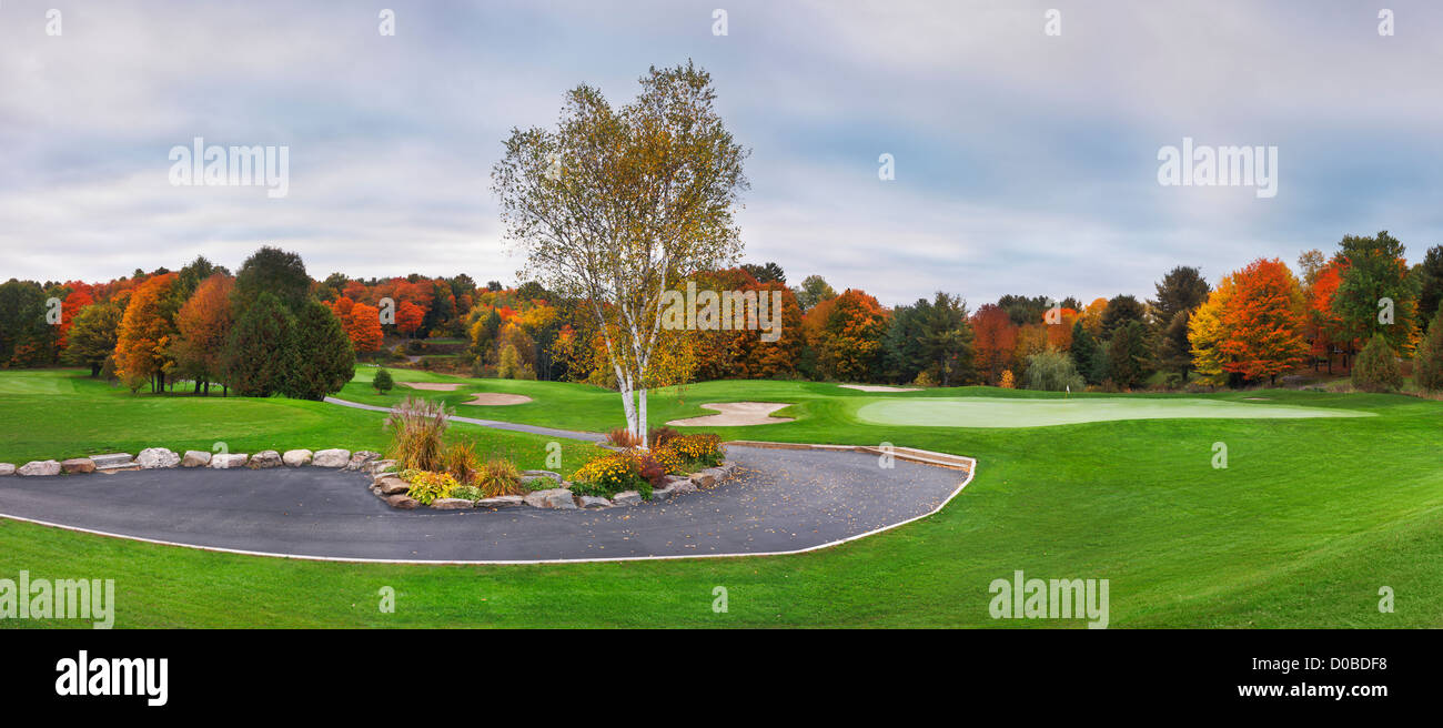 Golf course and colorful autumn trees, beautiful panoramic fall nature scenery at dawn. Muskoka, Ontario, Canada. - Stock Image