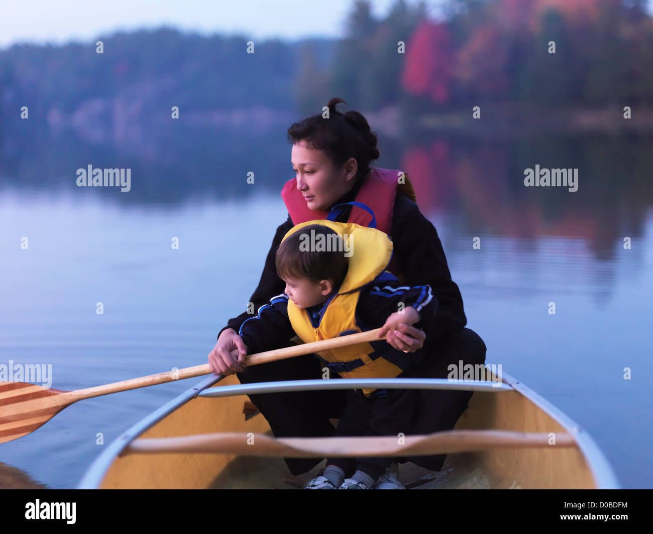 Mother with a three year old boy learning to paddle a canoe, fall nature scenery. Kilarney, Ontario, Canada. - Stock Image